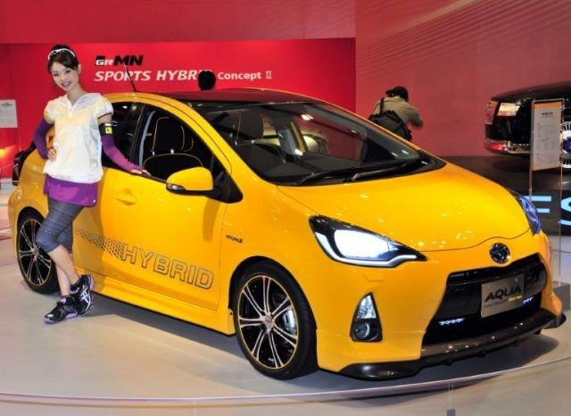 """A model displays Japanese auto giant Toyota Motor's compact hybrid vehicle """"Aqua"""" at a press preview of the Tokyo Motor Show on November 30, 2011"""