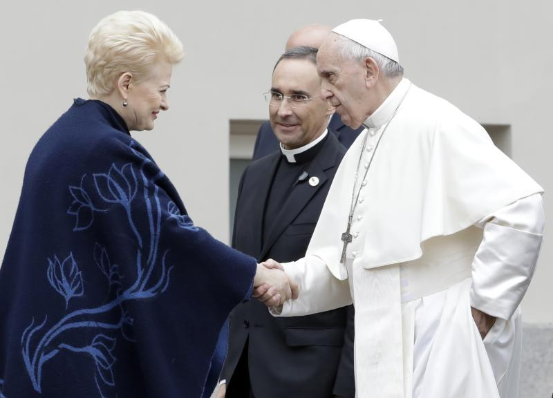 Pope Francis, flanked by papal trip organizer Mauricio Rueda Beltz, center, shakes hands with Lithuanian President Dalia Grybauskaite at the end of a meeting with authorities, civil society and diplomatic corps in the square in front of the Presidential Palace, in Vilnius, Lithuania, Saturday, Sept. 22, 2018. Pope Francis begins a four-day visit to the Baltics amid renewed alarm about Moscow's intentions in the region it has twice occupied. (AP Photo/Andrew Medichini)