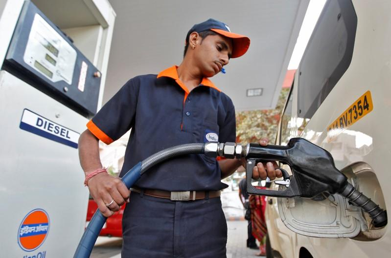 FILE PHOTO: A worker fills a vehicle with diesel at a fuel station in the western Indian city of Ahmedabad, India