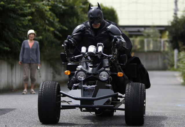 """REFILE - REMOVING EXTRANEOUS WORD A 41-year-old man going by the name of Chibatman leaves his home on his """"Chibatpod"""" in Chiba, east of Tokyo, August 31, 2014. The man, who dresses up as the comic book superhero Batman, came up with his moniker after adding a prefix of the first three letters of the city name, of which he roams on his three-wheeled motorcycle. However, unlike the hero from the Batman series, he rides around in his machine, designed from inspiration of the """"Batpod"""" from the movies The Dark Knight and The Dark Knight Rises, delivering smiles instead of fighting crime. REUTERS/Yuya Shino (JAPAN - Tags: SOCIETY ENTERTAINMENT TPX IMAGES OF THE DAY)"""