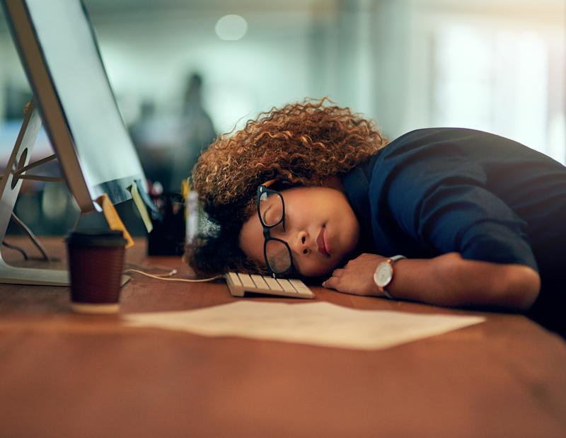 Shot of an exhausted young businesswoman sleeping at her desk during a late night at work