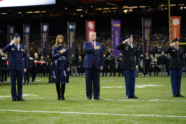 President Donald Trump, center, and first lady Melania Trump attend the NCAA College Football Playoff national championship game Monday, Jan. 13, 2020, in New Orleans. (AP Photo/David J. Phillip)