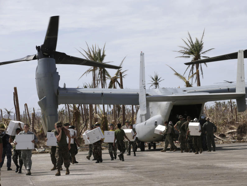 FILE - In this Wednesday, Nov. 20, 2013 file photo, U.S. troops unload relief supplies for typhoon survivors from a U.S. Marine MV-22 Osprey aircraft at Guiuan township, Eastern Samar province in central Philippines. The U.S. Marines' newest and in some quarters most controversial transport airplane is showing the world what it's got - for the sake of the victims of Typhoon Haiyan, and perhaps its own future. (AP Photo/Bullit Marquez)