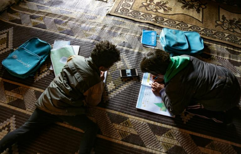 Young pupils follow a lesson on a mobile telephone at a camp for displaced Syrians in the village of Kafr Yahmoul in northwestern Idlib province