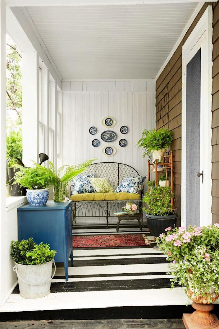 <p>A horizontally striped painted floor make this narrow porch look wider. </p>