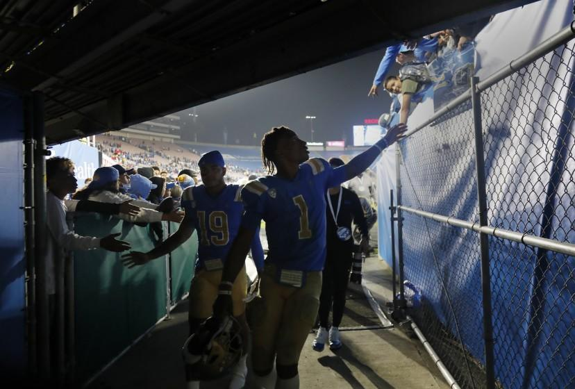 PASADENA, CA - SEPTEMBER 18, 2021: UCLA Bruins quarterback Dorian Thompson-Robinson (1) reaches out to fans as he heads to the locker room after a disappointing loss to Fresno State 40-37 at the Rose Bowl on September 18, 2021 in Pasadena, California.(Gina Ferazzi / Los Angeles Times)