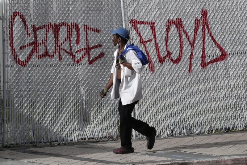 A man walks past graffiti in the aftermath of protests over the death of George Floyd, Sunday, May 31, 2020, in Miami. Protests were held throughout the country over the death of Floyd, a black man who died after being restrained by Minneapolis police officers on May 25. (AP Photo/Lynne Sladky)