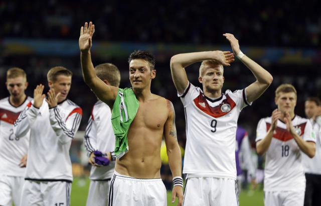 Germany's Mesut Ozil, left, and teammate Andre Schuerrle (9) celebrate after Germany defeated Algeria 2-1 in extra time during the World Cup round of 16 soccer match between Germany and Algeria at the Estadio Beira-Rio in Porto Alegre, Brazil, Monday, June 30, 2014. (AP Photo/Kirsty Wigglesworth)