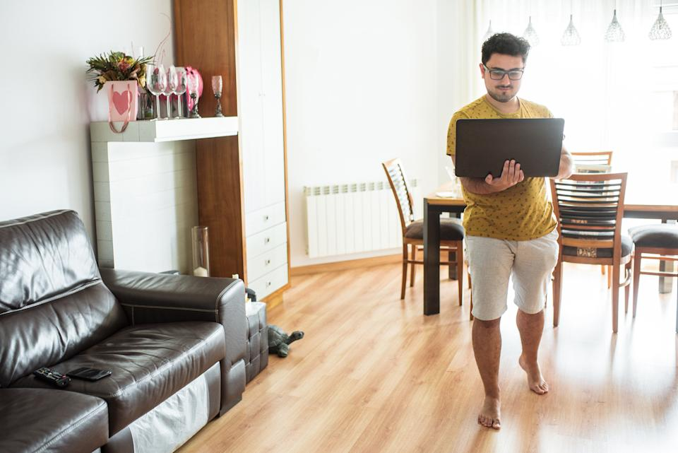 A young man working from home, walking and carrying his laptop with him