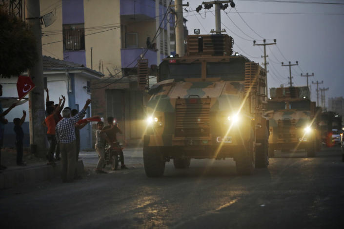 Shortly after the Turkish operation inside Syria had started, local residents cheer and applaud as a convoy of Turkish forces vehicles is driven through the town of Akcakale, Sanliurfa province, southeastern Turkey, at the border between Turkey and Syria, Oct. 9, 2019. (Photo: Lefteris Pitarakis/AP)