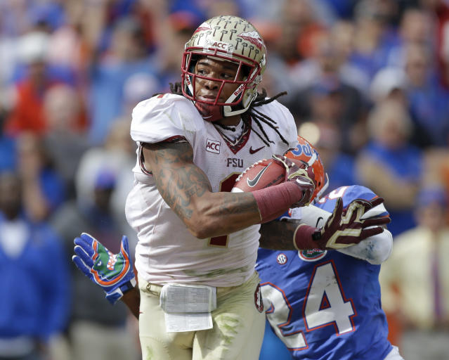 Florida State wide receiver Kelvin Benjamin breaks away from Florida defensive back Brian Poole (24) on his way to a touchdown on a 45-yard pass play in the first half of an NCAA college football game in Gainesville, Fla., Saturday, Nov. 30, 2013.(AP Photo/John Raoux)