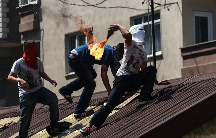 A protester prepares to throw a Molotov cocktail from a rooftop during clashes with Turkish police officers on July 26, 2015 in Istanbul (AFP Photo/Bulent Kilic)