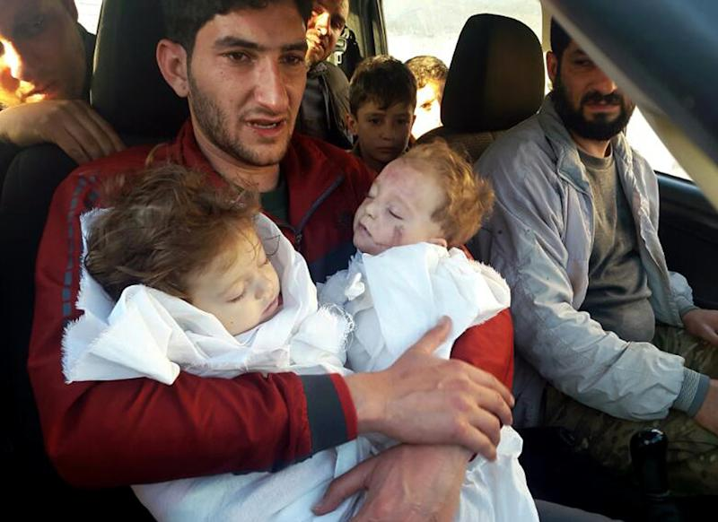 In this picture taken on Tuesday April 4, 2017, SAbdul-Hamid Alyousef, 29, holds his twin babies who were killed during a suspected chemical weapons attack, in Khan Sheikhoun in the northern province of Idlib, Syria. Alyousef also lost his wife, two brothers, nephews and many other family members in the attack that claimed scores of his relatives. The death toll from a suspected chemical attack on a northern Syrian town rose to 72 on Wednesday as activists and rescue workers found more terrified survivors hiding in shelters near the site of the harrowing assault, one of the deadliest in Syria's civil war. (Alaa Alyousef via AP)