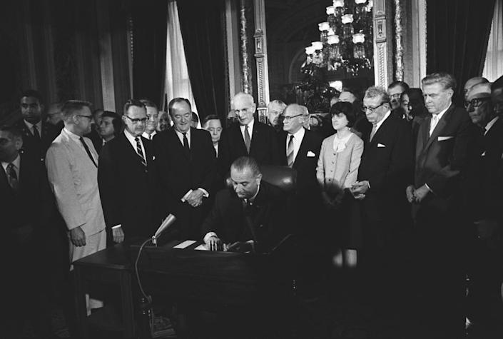 President Lyndon Johnson signing the Voting Rights Act on Aug. 6, 1965, in Washington, D.C. Luci Baines Johnson stands behind the president.