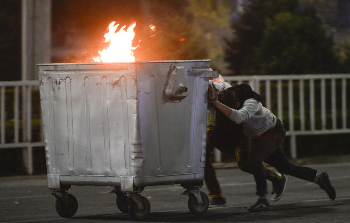 Image: Protesters push a burning trash can towards riot police during a rally against the results of a parliamentary vote in Bishkek, Kyrgyzstan (Vladimir Voronin / AP)