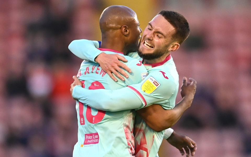 Andre Ayew of Swansea City celebrates with Matt Grimes after scoring his team's first goal during the Sky Bet Championship Play-off Semi Final 1st Leg match between Barnsley and Swansea City - Laurence Griffiths/Getty Images