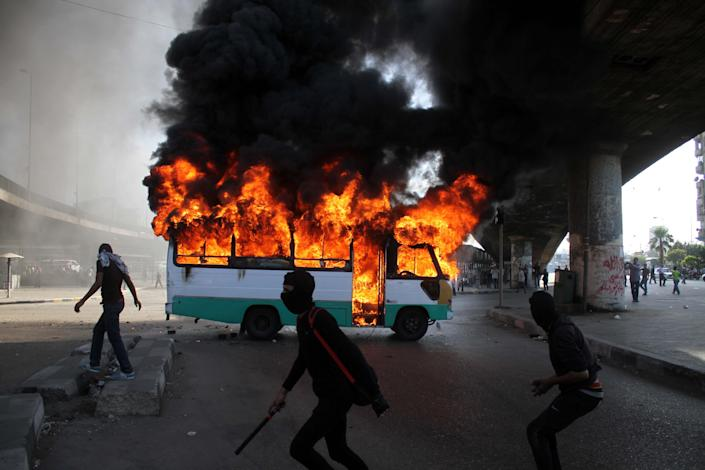 """Egyptian protesters clash near a bus belonging to Muslim Brotherhood supporters burns after it was reportedly set alight by anti- government protesters in Cairo, Egypt, Friday, April 19, 2013. Clashes erupted Friday between several hundred opponents and supporters of Egypt's Islamist president during a rally by his allies calling on him to """"cleanse the judiciary"""" of alleged supporters of the old regime. (AP Photo/Mostafa Elshemy)"""