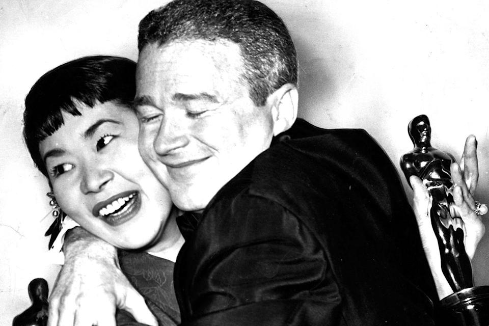 "<p>Best Supporting Actor and Actress winners Red Buttons and Miyoshi Umeki hugged it out after nabbing Oscars for their roles in <em>Sayonara</em>. The ceremony had multiple hosts including Bob Hope, Rosalind Russell, David Niven, James Stewart, Jack Lemmon, and ... Donald Duck<span class=""redactor-invisible-space"">.</span></p>"