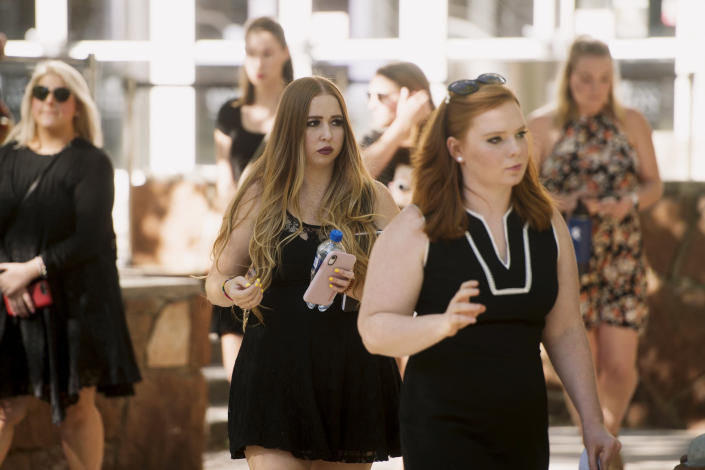 Ashley Fine, right, and Kennedy Stoner, center, arrive at a vigil for Mackenzie Lueck at the university in Salt Lake City on Monday, July 1, 2019. Friends and mourners gathered Monday night to remember Lueck, a Utah college student who was missing for nearly two weeks before police arrested a man accused of killing her and burying her charred remains in his backyard. (Jeremy Harmon/The Salt Lake Tribune via AP)