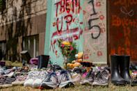 <p>Shoes were laid around the statue of Egerton Ryerson at Ryerson University as a memorial following the discovery of 215 bodies of students from residential schools in Kamloops, British Columbia. (Photo by Shawn Goldberg/SOPA Images/LightRocket via Getty Images)</p>