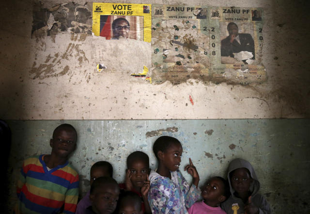 <p>Children stand beneath posters from the 2008 Zanu Pf election campaign in the Mbara suburb of Harare, Zimbabwe, Friday. Nov. 17, 2017. (Photo: AP) </p>