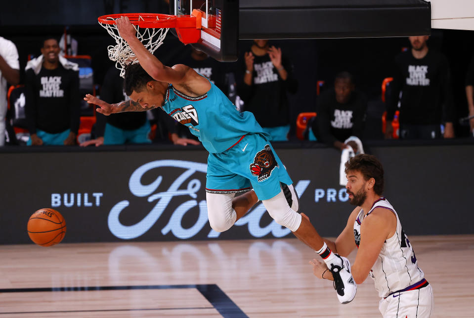 Brandon Clarke, left, of the Memphis Grizzlies' with a slam dunk over the Toronto Raptors during the second half of an NBA basketball game Sunday, Aug. 9, 2020, in Lake Buena Vista, Fla. (Kevin C. Cox/Pool Photo via AP)