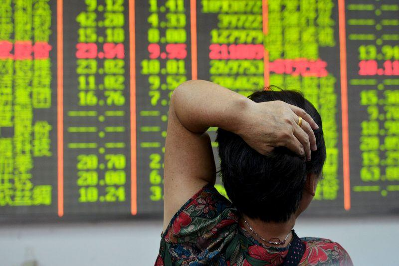 Investor looks at an electronic board showing stock information at a brokerage house in Hangzhou, Zhejiang province, China