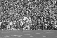 FILE - Miami Dolphins receiver Paul Warfield goes high in the air as he hauls in a pass from quarterback Bob Griese during the Super Bowl game against the Dallas Cowboys in New Orleans, in this Jan. 16, 1972, file photo. Trying to defend is Dallas' Cliff Harris (43). Warfield already had an NFL championship with the Cleveland Browns when they traded him to Miami for the No. 3 overall pick in the 1970 draft. That deal helped turn the Dolphins from losers to champions, though it took two years for Miami to reach its first Super Bowl. (AP Photo/File)