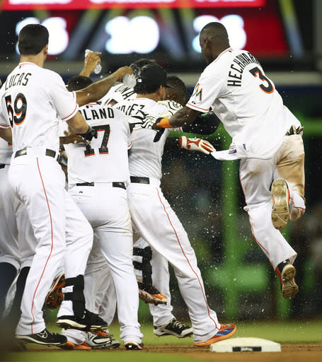 Miami Marlins players including Adeiny Hechavarria (3) celebrate with Marcell Ozuna after a game winning hit that drove home run during the 10th inning of a baseball game in Miami against the Arizona Diamondbacks, Thursday, Aug. 14, 2014. The Marlins won 5-4 in the 10th inning. (AP Photo/J Pat Carter)