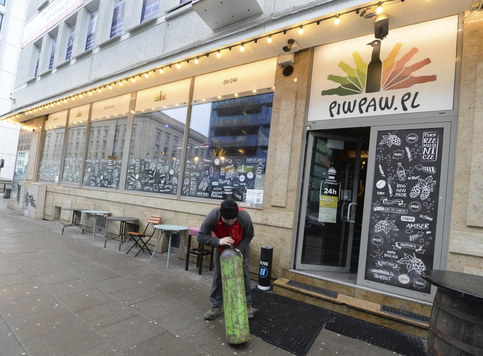 A man delivers a supply of heating gas to Warsaw's popular Piw Paw pub in Warsaw, Poland, Monday, Jan. 25, 2021, a business that is struggling to survive under lockdown by organizing legal, small-scale educative meetings and courses for beer lovers. (AP Photo/Czarek Sokolowski)