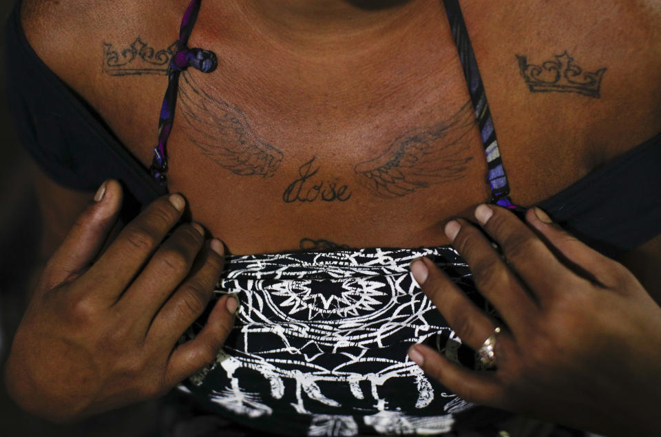 A 27-year-old sex worker who goes by the name Angora shows the tattoo she had done to remember her 14-year-old brother Jose, who was murdered back home in Honduras after becoming an assistant to a group of horse thieves, as she waits for clients outside the Revolution subway station in Mexico City, Tuesday, March 9, 2021. Angora says the competition for clients since the coronavirus pandemic began has exacerbated discrimination against immigrant sex workers from Central America in Mexico City. (AP Photo/Rebecca Blackwell)
