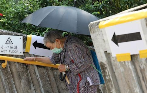 An elderly Hong Kong resident walks up the stairs to take a Covid-19 test at Kwun Tong Government Secondary School. Photo: K. Y. Cheng