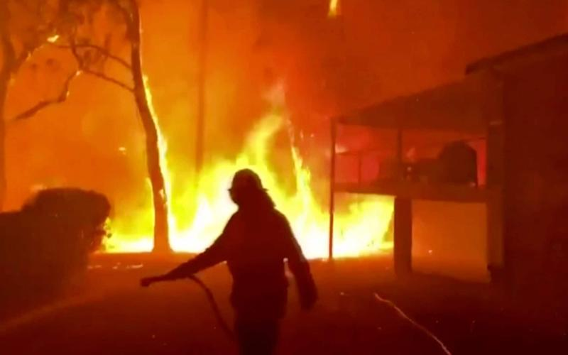 A firefighter sprays water on a blaze nearing a home in Blackheath, New South Wales, on December 22 - Twitter@NSWRFS