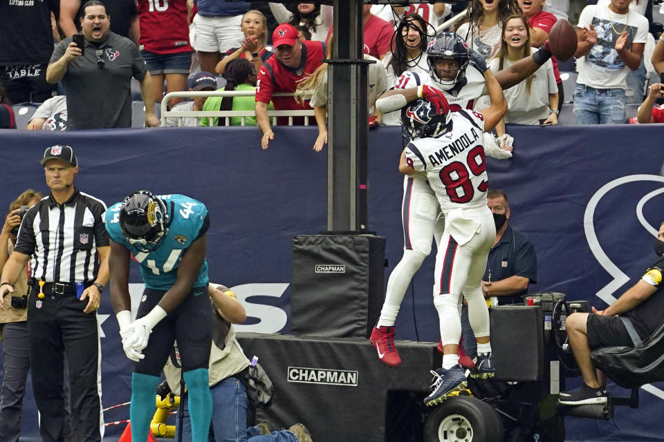 Houston Texans' David Johnson (31) celebrates his touchdown catch with Danny Amendola (89) as Jacksonville Jaguars linebacker Myles Jack (44) looks down at the goal line during the first half of an NFL football game Sunday, Sept. 12, 2021, in Houston. (AP Photo/Sam Craft)
