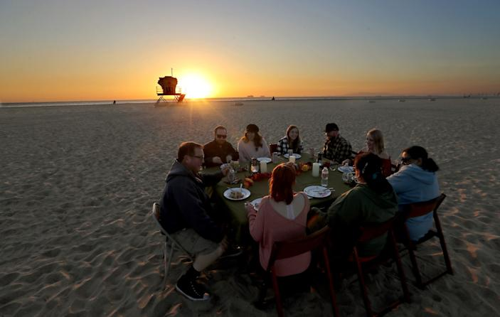 Nine people sit behind plates of food at a round table on the sand. In the background, the sun sets behind a lifeguard tower.
