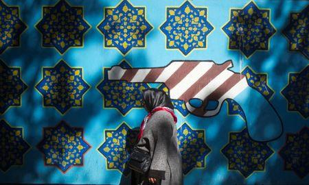 An Iranian woman walks past an anti-U.S. mural on the wall of the former U.S. embassy in Tehran October 12, 2011. REUTERS/Morteza Nikoubazl/Files