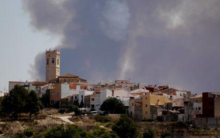 The smoke of a wildfire is seen behind the village of Teulada near Alicante, Spain September 5, 2016. REUTERS/Heino Kalis
