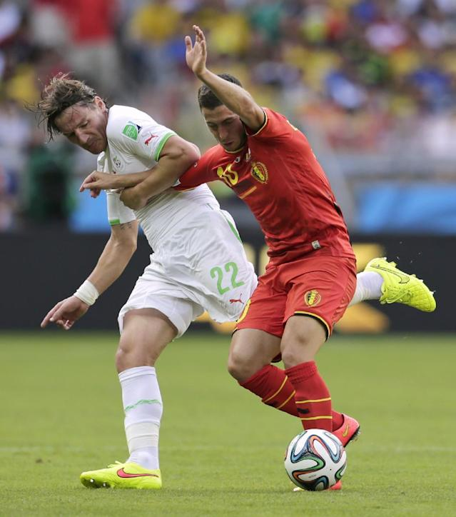 Algeria's Mehdi Mostefa, left, holds on to Belgium's Eden Hazard during the group H World Cup soccer match between Belgium and Algeria at the Mineirao Stadium in Belo Horizonte, Brazil, Tuesday, June 17, 2014. (AP Photo/Petr David Josek)