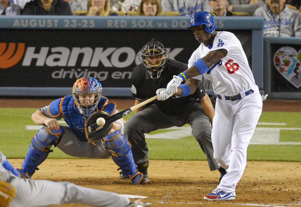 Los Angeles Dodgers' Yasiel Puig, right, hits a sacrifice fly that scored Adrian Gonzalez as New York Mets catcher John Buck, left, and home plate umpire Chad Fairchild look on during the sixth inning of their baseball game, Monday, Aug. 12, 2013, in Los Angeles. (AP Photo/Mark J. Terrill)