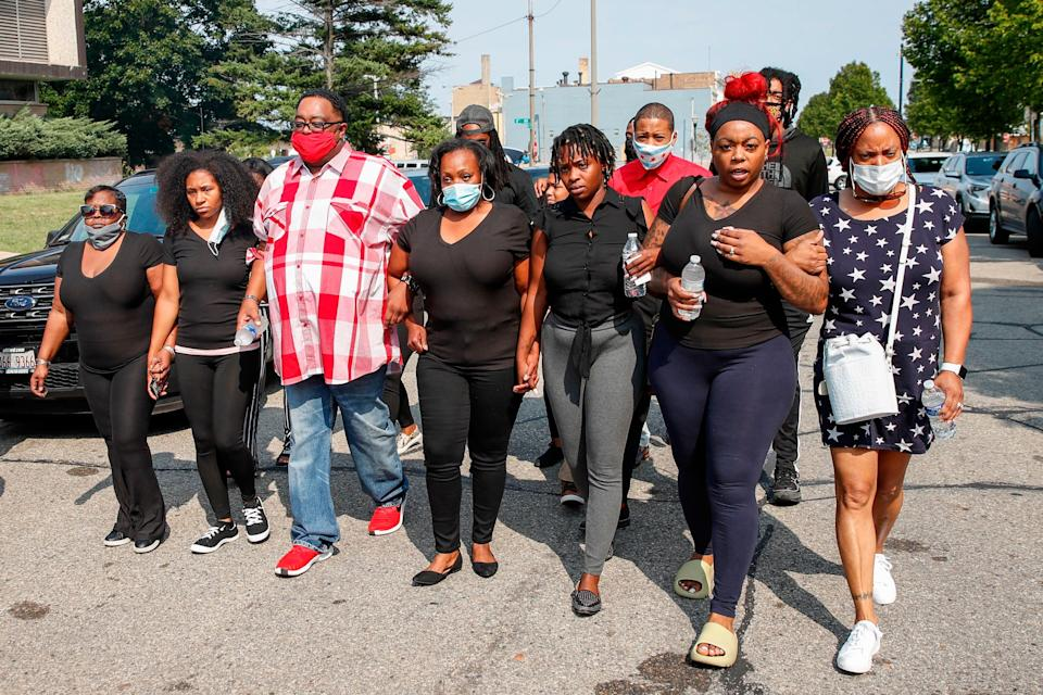 jacob blake's relatives march down the street linking arms
