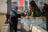 Israeli soldiers check a Palestinian women as she wait to cross the Qalandia checkpoint between the West Bank city of Ramallah and Jerusalem, to attend the second Friday prayers in the al-Aqsa mosque during the Muslim holy month of Ramadan, Friday, April 23, 2021. A limited number of Palestinian residents who carry both a travel permit and a vaccination document, are allowed to cross into Israel to attend the prayers at al-Aqsa mosque, due to the coronavirus pandemic. (AP Photo/Majdi Mohammed)