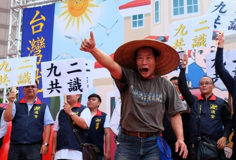 """Pro-unification activists wave banners that read """"92 consensus"""" in reference to a tacit agreement between Taipei and Beijing that there is only """"one China"""""""