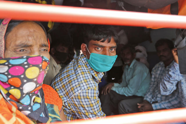 """Daily wage laborers, returning from Mumbai travel to their villages amid Coronavirus concerns in a crowded train coach in Prayagraj , India, Sunday, March 22, 2020. India is observing a 14-hour """"people's curfew"""" called by Prime Minister Narendra Modi in order to stem the rising coronavirus caseload in the country of 1.3 billion. For most people, the new coronavirus causes only mild or moderate symptoms. For some it can cause more severe illness. (AP Photo/Rajesh Kumar Singh)"""