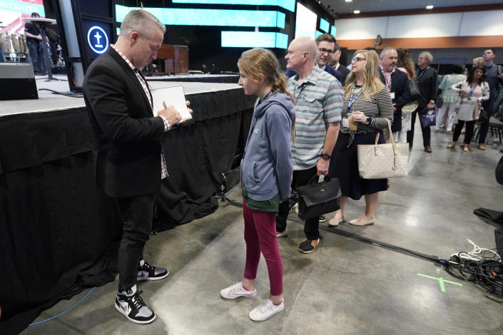 Outgoing Southern Baptist Convention President J. D. Greear, left, autographs a book after the denomination's annual meeting adjourned Wednesday, June 16, 2021, in Nashville, Tenn. (AP Photo/Mark Humphrey)