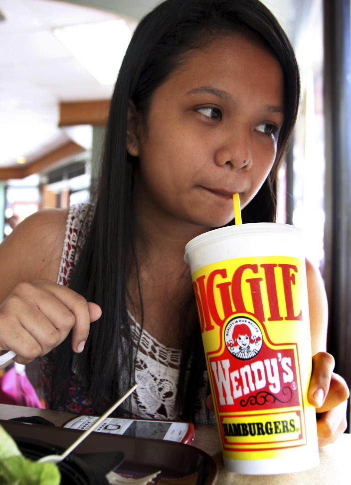"Pearl Ganotisi sips from her 24-ounce of soda drinks as she takes her meal in an American hamburger chain Friday, June 1, 2012 in Manila, Philippines. New York Mayor Michael Bloomberg has proposed a ban on the sale of large sodas and other sugary drinks in restaurants, delis and movie theaters in the hopes of combating obesity. Under his plan, sugary drinks would be limited to 16 fluid ounces _ almost half a liter. Around the world, portion sizes are generally smaller. Perceptions of American overconsumption have been fueled by films such as ""Super Size Me"" and the spread of U.S. fast-food chains. (AP Photo/Pat Roque)"