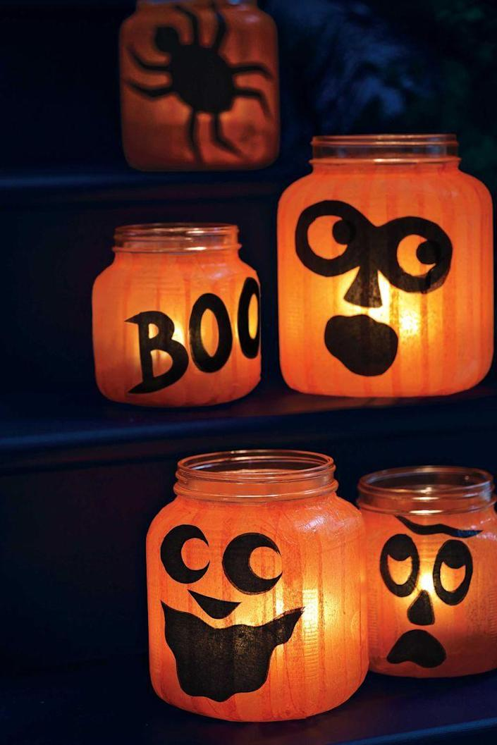 """<p>Create a quirky patch of pumpkins using round glass holders and tissue paper.</p><p><a href=""""https://www.womansday.com/home/crafts-projects/how-to/a5994/halloween-craft-how-to-pumpkin-jar-lights-124116/"""" rel=""""nofollow noopener"""" target=""""_blank"""" data-ylk=""""slk:Get the tutorial for Spooky Candle Luminaries."""" class=""""link rapid-noclick-resp""""><em>Get the tutorial for Spooky Candle Luminaries.</em></a></p>"""