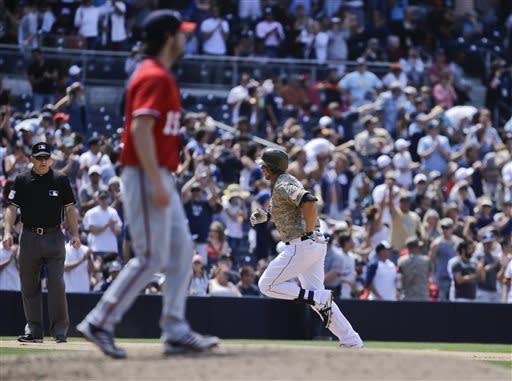 San Diego Padres' Kyle Blanks, right, rounds the bases with a fifth-inning home run as Washington Nationals pitcher Dan Haren, foreground, walks off the mound during a baseball game in San Diego, Sunday, May 19, 2013. (AP Photo/Lenny Ignelzi)