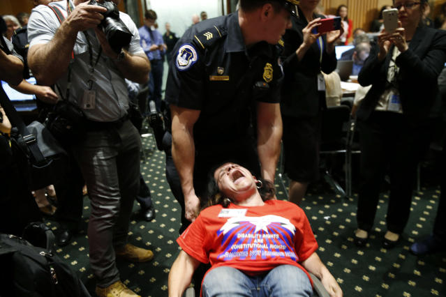 <p>A protester is removed by a Capitol Hill police officer during a Senate Finance Committee hearing on the latest Republican effort to repeal and replace the Affordable Care Act on Capitol Hill in Washington, U.S. September 25, 2017. (Photo: Kevin Lamarque/Reuters) </p>