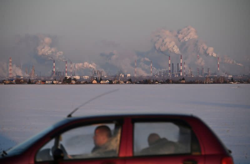 FILE PHOTO: A car drives past the Gazprom Neft's oil refinery in Omsk