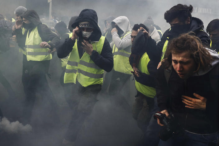 Protestors protect themselves as tears gas fill near the Champs Elysees in Paris on Dec. 8, 2018 during a mobilisation gainst rising costs of living they blame on high taxes. (Photo: Sameer Al-Doum /AFP/Getty Images)